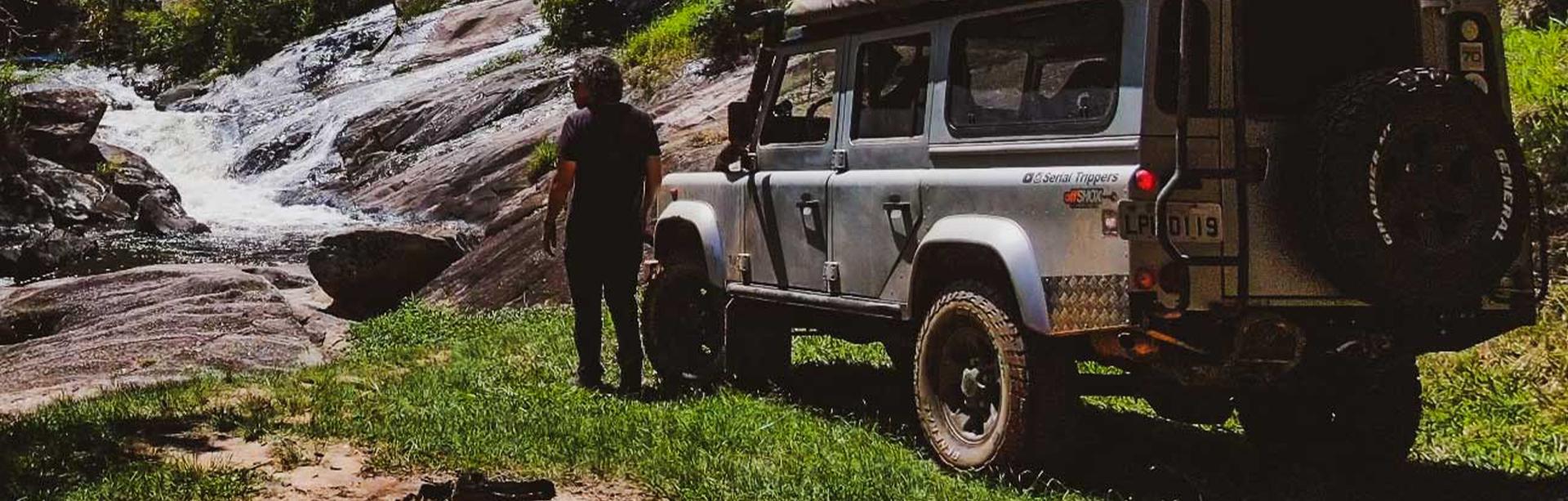 Expedição General Tire | Ep 6 - Paraty (Imagem Pochollo de pé ao lado do seu land rover em frente a uma cachoeira)